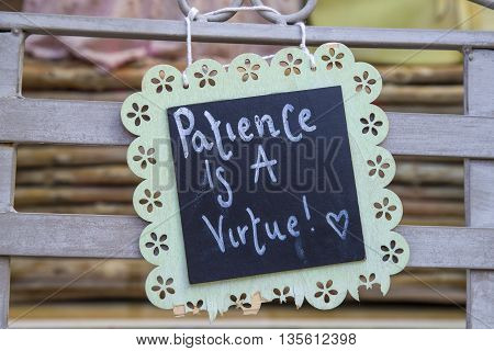A philosophical Patience is a Virtue sign attached to a bench.