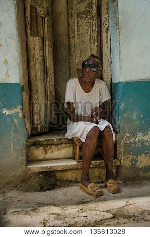 HAVANA - CUBA JUNE 19, 2016: A blind old woman wearing dark glasses sits on the stoop of her home, one of thousands of deteriorating and decaying buildings in La Habana Vieja.