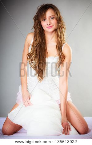 Sleep and wake up concept. Pretty young woman in curly long brown hair with pillow on gray background.