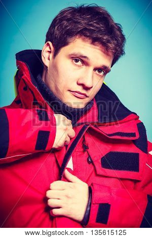 Young male in protective clothing. Man in waterproof suit. Danger action outdoor concept.