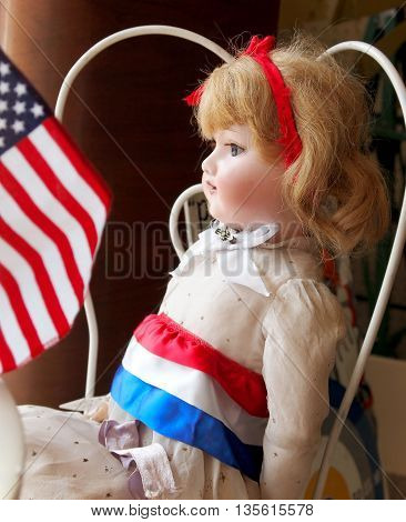 A pretty vintage doll is dressed for the Fourth of July gazing out a window with an American Flag.