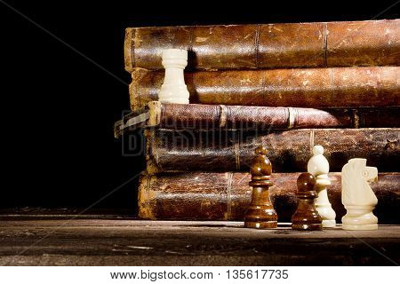 Old books and chess pieces on a black background
