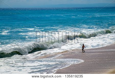 Big wave at a sunny summer day on the Dreamland beach in Bali. Crazy man running into the huge wave , Indian ocean, Java sea, Indonesia.