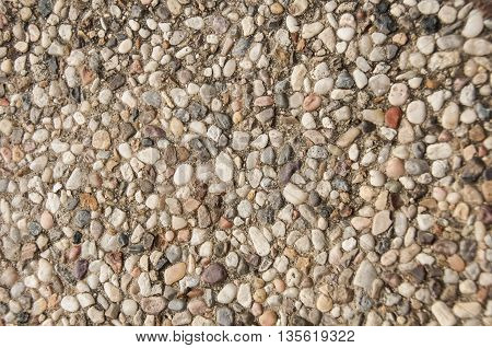 The pea gravel that composes a pool deck.