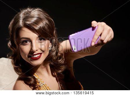 woman in dress studio portrait in hollywood style light on black background. making selfie
