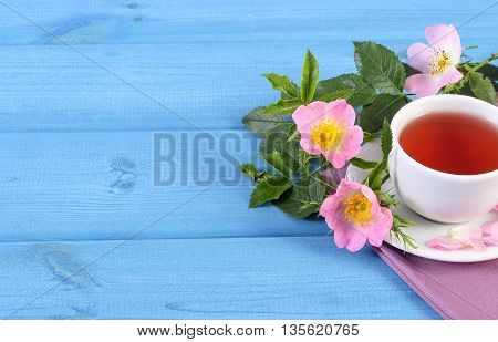 Cup Of Tea And Wild Rose Flower On Blue Boards, Copy Space For Text
