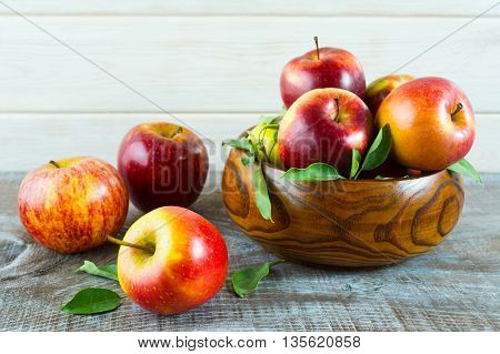 Fresh apples in the wooden bowl. Ripe fruits as healthy eating or vegetarian food concept.