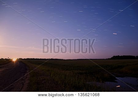 Scenic night landscape with fields forests and road against the evening sky with the stars in the form of tracks taken with a long exposure