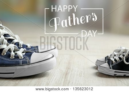 Happy father's day concept. Big and small shoes on wooden floor