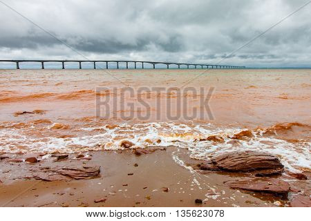 The long Confederation Bridge linking Prince Edward Island to the mainland is visible behind red muddy surf