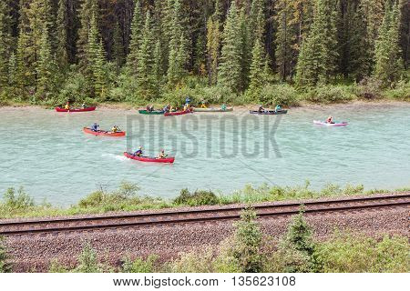 Canoeists stopping by railway tracks in the Bow River in Banff Alberta