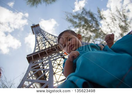 Infant seating under replica of Eiffel Tower