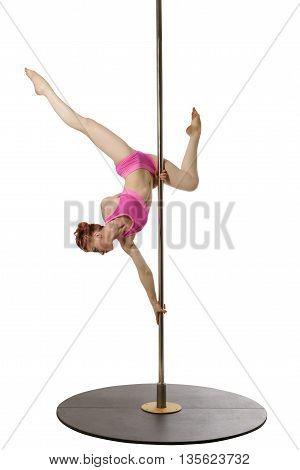 Redhead female gymnast posing upside down on pylon
