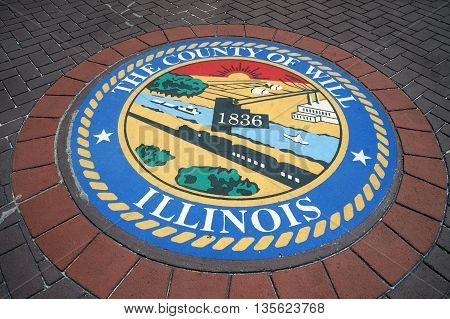 JOLIET, ILLINOIS / UNITED STATES - JUNE 3, 2015: The Seal of Will County, Illinois decorates the sidewalk in front of the Will County Office Building in downtown Joliet.