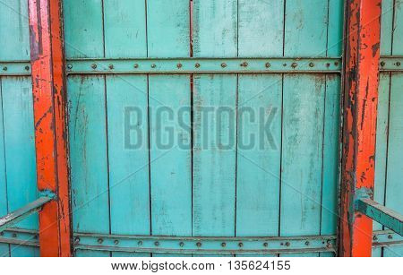 image of old blue wooden wall and nut stick on wood panel with iron bar.
