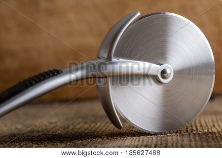Circular Pizza Cutter on wooden rustic background