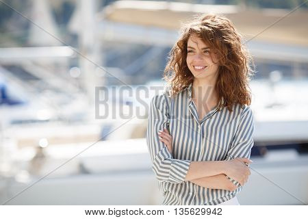 Stylish young woman with gray eyes,curly red hair and sweet smile,dressed in white pants and a bright striped shirt,walks alone on the pier next to the yacht club,stands on the background of the sea yachts and boats in summer time in fresh air
