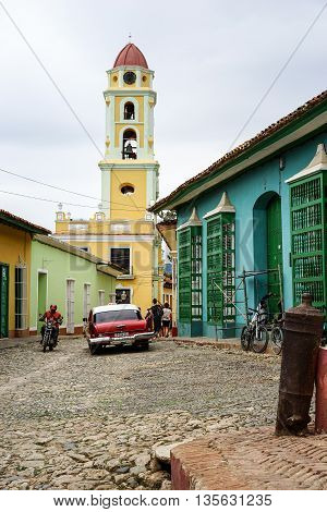 Trinidad Cuba - January 14 2016: Typical scene of one of streets in the center of Trinidad Cuba - colonial architecture people walking around vintage american car
