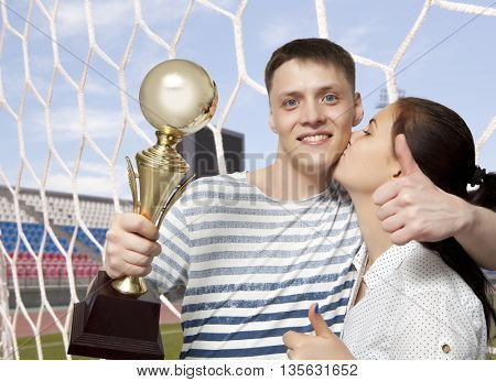 Man holding up a gold trophy cup as a winner in a competition