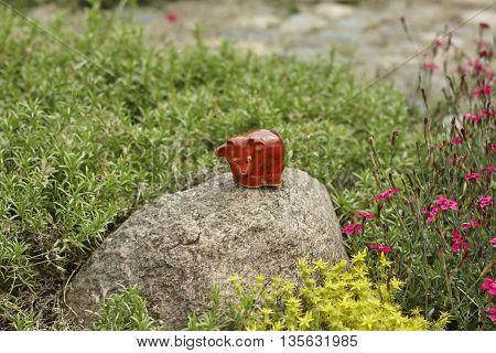 red bull toy on stone in garden close up