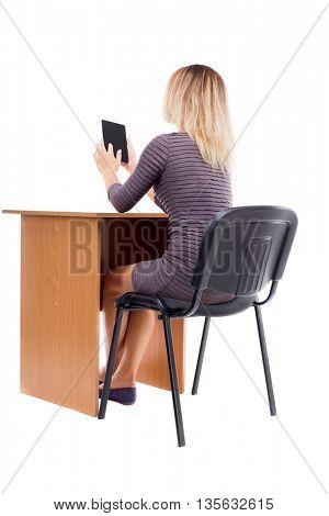 back view of woman sits by the table and looks at the screen of the tablet.  Rear view people collection. backside view of person. Isolated over white background.Girl at office desk reading an e-book.