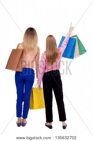 back view of  two pointing women  with shopping bags. backside view of person.  Rear view people collection. Isolated over white background. Two girls with paper bags looking at something in the sky.