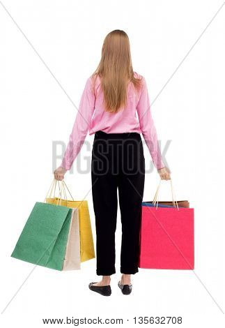 back view of woman with shopping bags .  backside view of person.  Rear view people collection. Isolated over white background. The girl in the pink shirt is held in both hands with shopping bags.