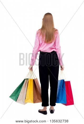 back view of woman with shopping bags . Isolated over white background. A girl in pink shirt stands with lots of shopping bags and looking in front of him.