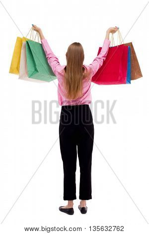 back view of woman with shopping bags . beautiful brunette girl in motion.  backside view of person.  Rear view people collection.  A girl in pink shirt stands with arms raised to the top of the bags.