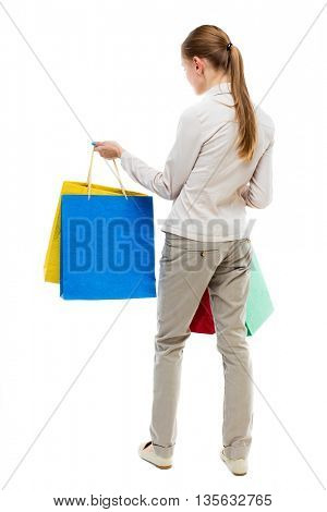back view of woman with shopping bags . beautiful brunette girl in motion.  Rear view people collection. Isolated over white background. Girl in gray jeans holding at arm's length paper bags.