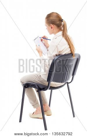 back view of young beautiful  woman sitting and  takes notes in a notebook.  girl  watching. Rear view people collection.  Isolated over white background.  girl sits in a light denim suit and writes.