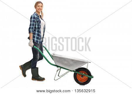 Full length profile shot of a female gardener pushing an empty wheelbarrow isolated on white background