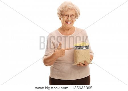 Senior woman holding a bag of potato chips and pointing to it with her finger isolated on white background