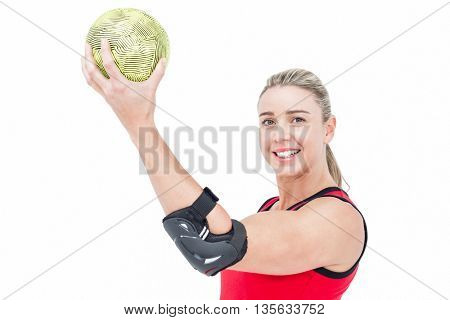 Female athlete with elbow pad holding handball on white background