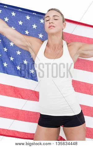 Female athlete holding American flag with closed eyes on white background