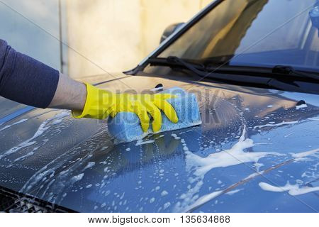 a turquoise car is washing in soap suds