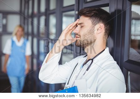Close-up of male doctor suffering from headache while standing at hospital