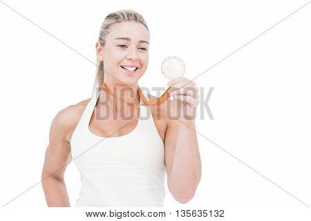 Happy female athlete holding medal on white background