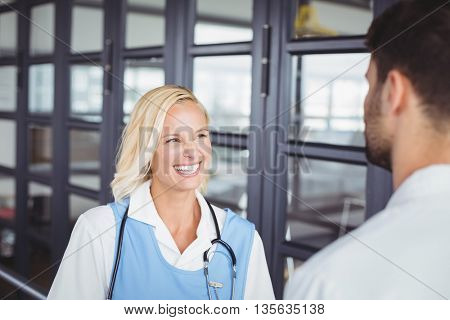 Smiling female doctor discussing with colleague while standing at hospital