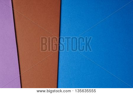 Colored cardboards background in blue brown purple tone. Copy space. Horizontal