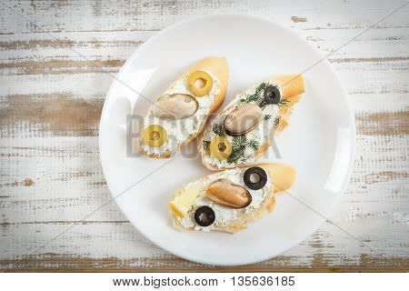 Tasty various italian sandwiches with seafood against rustic wooden background. Crostini with cheese mussels and sliced olives on white plate horizontal top view