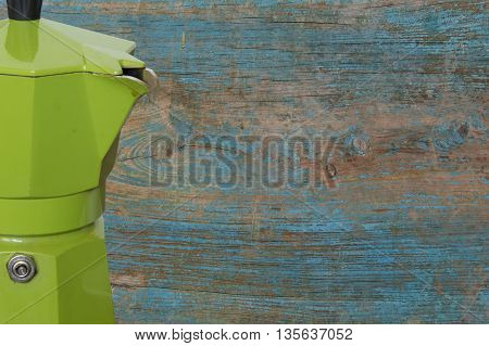 Moka coffee maker of green color on a retro background
