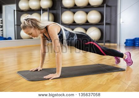 Woman Doing Pushups On Exercise Mat In Gym