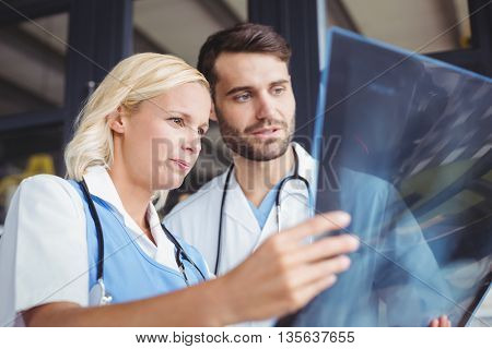 Doctors analysing X-ray while standing at hostiptal