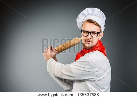 Enraged chef cook brandishing with a rolling pin. Studio shot.