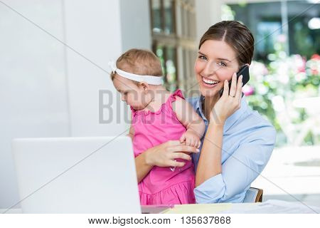 Happy woman talking on mobile phone while sitting with baby girl at home