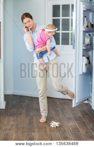 Woman closing refrigerator door with leg while carrying baby girl at home