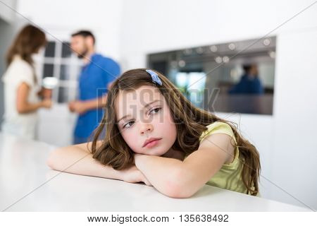 Unhappy girl looking away on table against parents at home