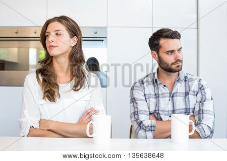 Upset couple with arms crossed sitting by table at home