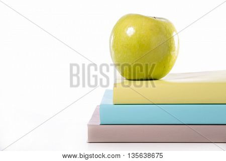 book and green apple